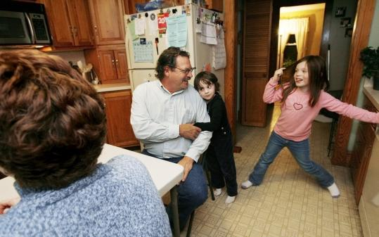 Steve Drouin and his wife, Jean, with their grandchildren, Rebecca Wilson, 4 (middle), and Jenna Wilson, 7, at home in Northfield, N.H.