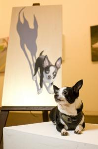 Denise Lindquist's dog Ari sits in front of a portrait by Jane O'Hara. ''Ari's Night'' is on display at Brickbottom Gallery in Somerville as part of ''Best In Show: Artists and Their Dogs.''