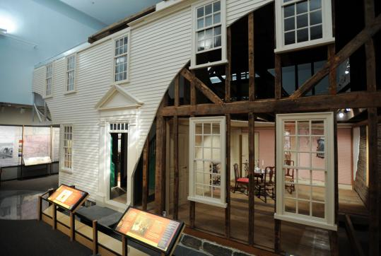 The front of the Ipswich House has a cutaway, displaying a parlor decorated from the 1760s era, on display at the Smithsonian.