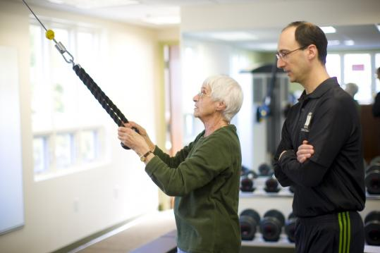 Eric Stutman works with Joan Wayne of Wayland during a personal training session at his gym, One2One BodyScapes in Wayland.