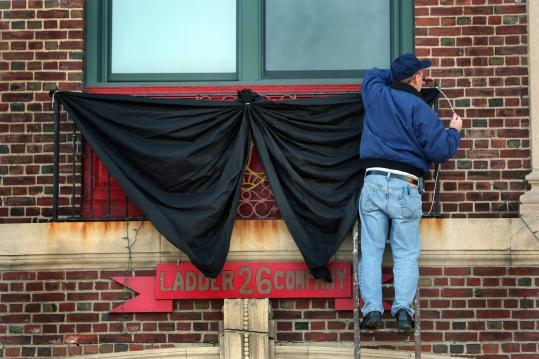 Canton firefighter Butch King draped black bunting on the front of the Ladder 26 firehouse on Huntington Avenue.