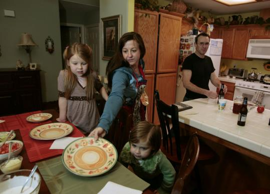 Cindy Reilly set the dinner table for her children, Isabella, 7, (left) and Sierra, 4, and her husband Mike in their home in Nipomo, Calif. The family has decided to escape California's high cost of living by moving to Colorado next month.