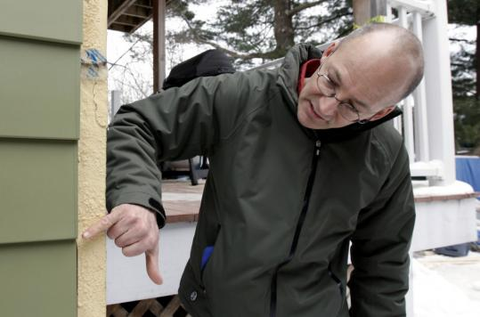 Alex Cheimets showed the thick insulation on his two-family house in Arlington. His project, which cost $100,000, is being used to study super insulation as a way to conserve energy.