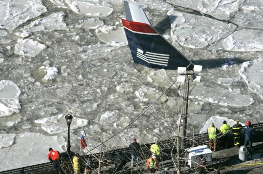 Only the tail section of the US Airways Airbus A320, which crashed on Thursday, was visible in the ice-choked Hudson River yesterday. Divers have been searching the cold, murky water for the missing left engine, which may be buried in sediment.