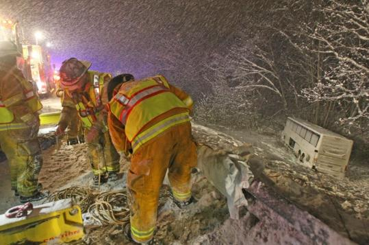Rescue workers attended to the crash scene of a bus that veered off the Massachusetts Turnpike and down an embankment after hitting a guardrail Sunday night. Five of the 30 passengers were hospitalized with minor injuries.