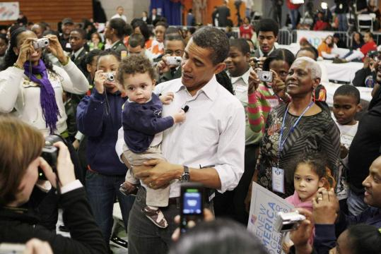 Barack Obama held Charles Rollins, 1, yesterday as he visited Calvin Coolidge High School yesterday in Washington D.C.