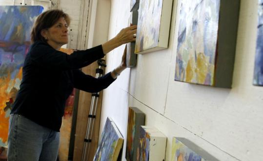 Framingham artist Lynette Haggard, seen setting up a display in her Saxonville studio, and Nancy Natale will open a joint show featuring their encaustic, or hot-wax, paintings next week at Maynard's Artspace Gallery.