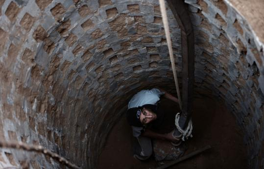 A Palestinian worked yesterday to rebuild a tunnel in Rafah, Gaza, near Egypt. Smugglers' tunnels targeted in Israel's campaign against Hamas were active again at the Egyptian border.