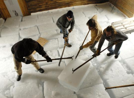 Shawn Patrick Ouellette/Portland Press HeraldVolunteers stack blocks of ice harvested from Thompson Pond.