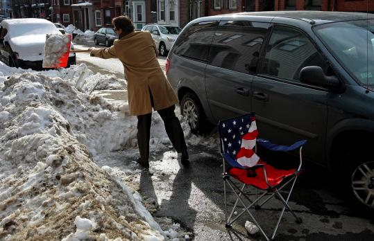 Chris Powers took advantage of warmer temperatures yesterday to clean up his marked parking spot on N Street in South Boston.