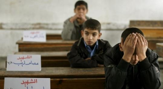 Mohammed Kutkut, 14, covered his face as he sat next to a sign for his slain friend, Ahed Qaddas, in Jebaliya, Gaza Strip.