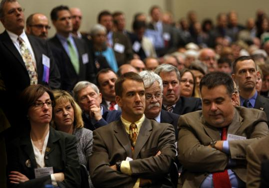 Members of the Massachusetts Municipal Association - including (seated in front row) Vanessa Hale of Southborough and Mark Purple and John Petrin, both Ashland officials - listened Friday to Governor Deval Patrick's grim news about local aid cuts.