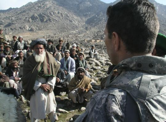 US Colonel Greg Julian with Afghan village elders in Inzeri yesterday. US commanders distributed $40,000 and apologized to relatives of 15 people killed in a recent US raid.