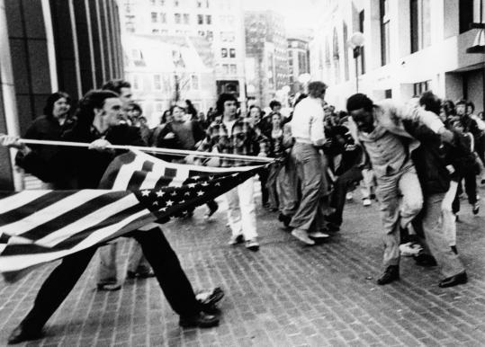The city's demographics have changed since busing began, says Ted Landsmark, who was the target of this angry demonstrator brandishing an American flag during the school busing riots on April 5, 1976.