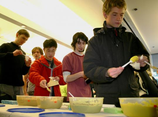 MIT students (above) line up to taste hummus recipes. Below: freshman Victoria Cheng samples Picante Soy hummus.