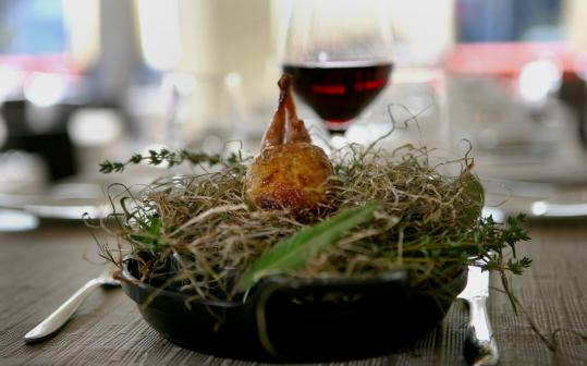 Quail cooked in hay is brought to the table in a cast iron skillet.