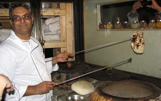 Chef P.K. Ahluwalia taking a naan from his tandoor oven. His restaurant uses one tandoor to bake breads, another for meats.