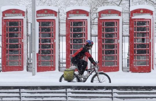 A cyclist rode through the snow in the morning rush hour in central London yesterday. The heavy snow caused nearly 800 flight cancellations and hundreds of school closures.