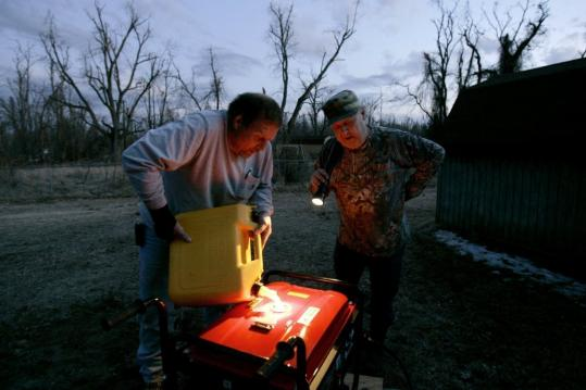 David Strange filled Jimmy Timmons's portable generator with fuel on Sunday in Columbus, Ky., after electric service to his house was knocked out following a winter storm.