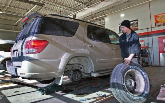 Erik Pizano put tires on a Massachusetts vehicle at Town Fair Tire Center in Nashua. The company is fighting the tax policy.