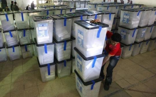An Iraqi election worker moved ballot boxes at a ballot counting center in Baghdad yesterday.