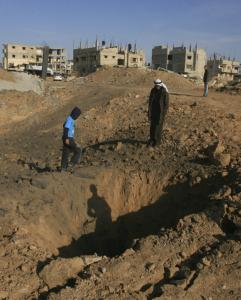 Palestinians stood near a crater yesterday made by an Israeli airstrike near the border of Egypt and Rafah, southern Gaza Strip. The offensive was in response to rockets fired on Israel.