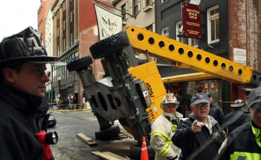 Boston firefighters and emergency personnel at the scene of a crane collapse yesterday on West Street in Downtown Crossing.