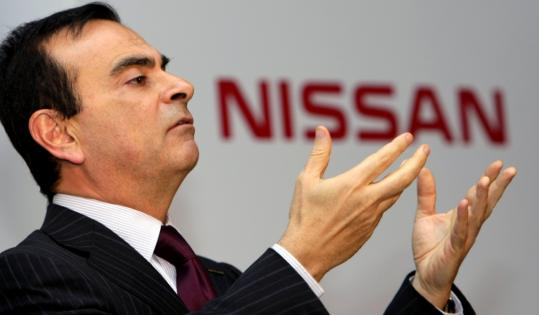 Nissan Motor's chief executive Carlos Ghosn gestures during a press conference at its Tokyo headquarters yesterday. Nissan expects a $2.9 billion net loss for fiscal year through March.