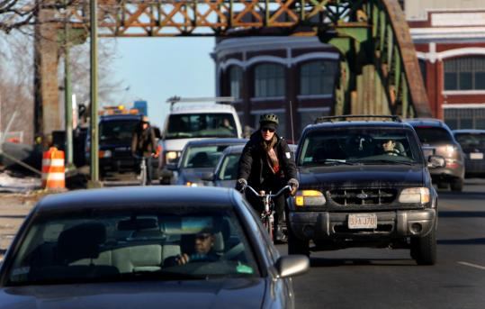 Bicyclists and motorists traveled into Boston on the BU Bridge. Construction at left closed down one lane, congesting traffic.