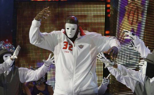 The man behind the mask is Shaquille O'Neal, performing with a dance troupe during introductions.