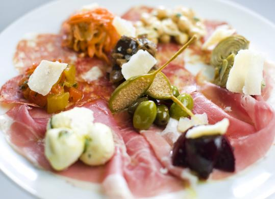 The antipasti platter offers house-made prosciutto and salami, olives, tiny artichoke hearts, and Parmigiano.
