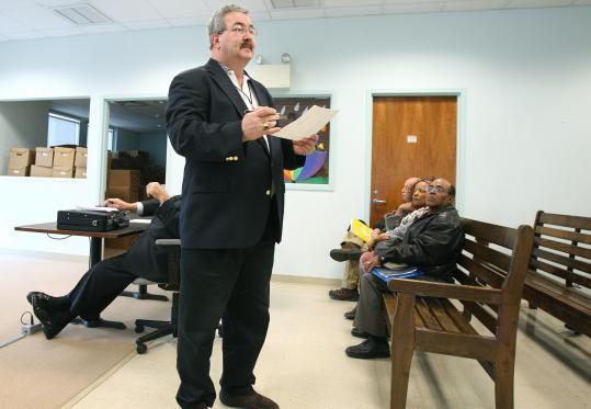 In Brockton court, Ron Fredey (standing) of the Greater Brockton Center for Dispute Resolution asks if any are willing to mediate their claim.