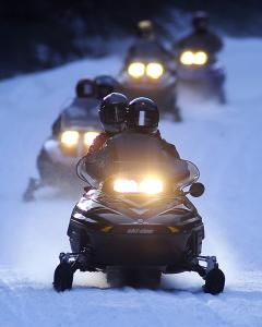 With safety in numbers, a pack of snowmobilers cruising for adventure navigate a trail in Bartlett, N.H.