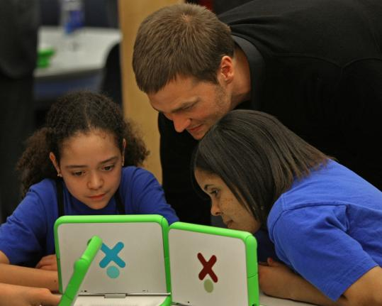 Myesha Neely (left) and Meyling Galvez check out the donated laptops with Tom Brady looking on.