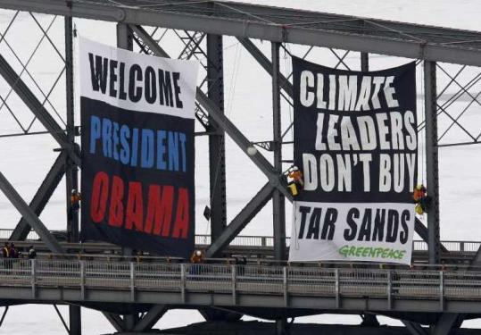 Greenpeace activists unfurled a banner on an Ottawa bridge yesterday, urging President Obama to oppose oil sands