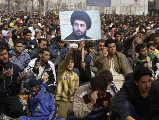 Followers of radical Shi'ite cleric Moqtada al-Sadr, seen on a poster at center, attended prayers in Baghdad yesterday.