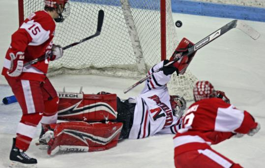 With his team two men down, Northeastern goalie Brad Thiessen sprawls to make a save.