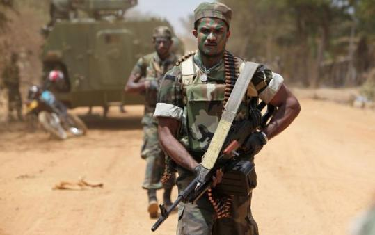 A Sri Lankan soldier carried his machine gun yesterday near the fighting. Tamil rebels called for a cease-fire.