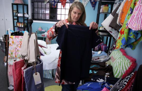 Bonnie Hertberg organizes inventory at the Coop in Hingham Square, which she cofounded in December with three other ''mompreneurs.''