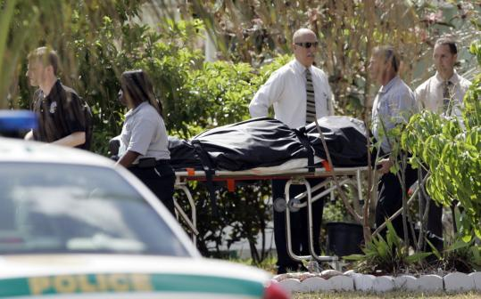 A body was carried from a Miami couple's house yesterday. Police said the man killed himself, his wife, and their two daughters.