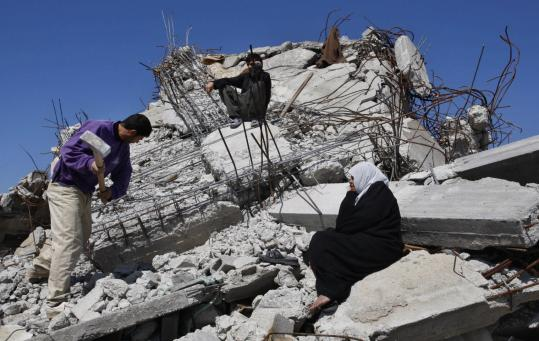 Hatem Moussa/Associated PressA Palestinian family worked on the rubble of a house in Jebaliya, in the northern Gaza Strip, that was destroyed in Israel's attack. Representatives of donor countries meeting Egypt tomorrow will be asked to pledge at least $2.8 billion in aid to Gaza.