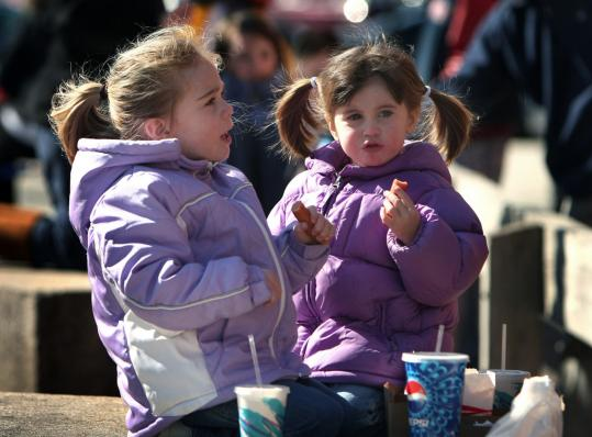 Three-year-old Brennah Hynes (left), of South Boston, and her sister Millie, 2, enjoyed their hot dogs yesterday outside Sullivan's. The hot dog and burger shack, an institution in South Boston since 1951, serves its traditional ''snap dogs'' this time of year.