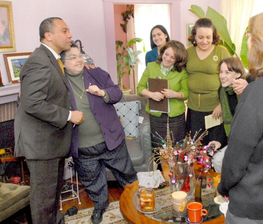 Governor Deval Patrick hugged Teresita Alicea at her Springfield home after speaking to Alicea and her neighbors about his proposed gas tax increase. Yoliany Ortiz (from left), Elizabeth Cardona of Patrick's Western Massachusetts office, Iris Yolanda Van Derdys-Ortiz, and Becky Lartigue attended the session.