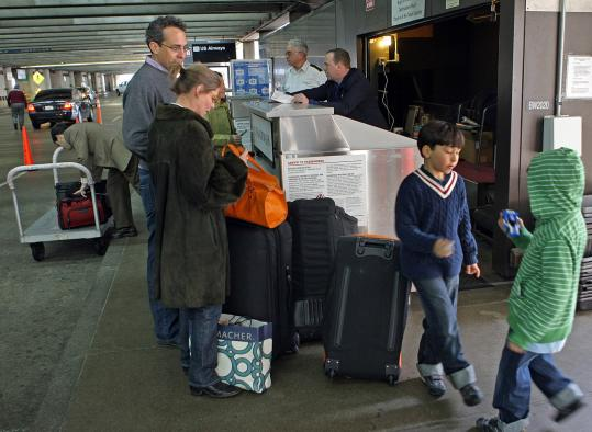 Ben and Jill Kaplan of Newton traveled with their sons Graham and Ian (in green) and lots of luggage at Logan International Airport. Ben Kaplan said using public transit would be difficult: ''We'd be more likely to take a cab.''