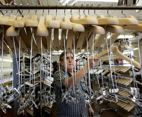 Dario Paramo assembles hangers at Henry Hanger Company, where managers are trying to cut costs.