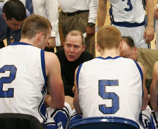 Brandeis coach Brian Meehan huddles up with his players.