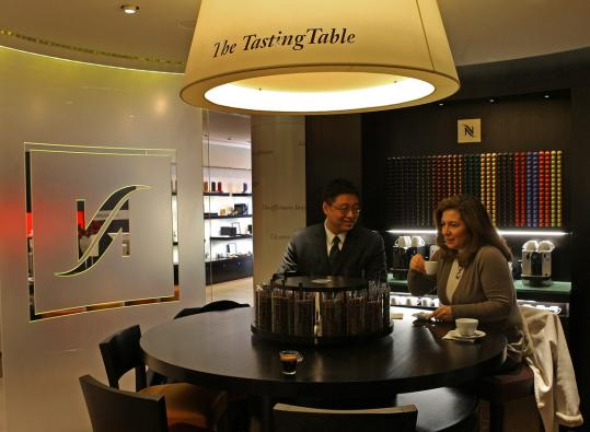 Above: James Liu and Dina Debs drink samples at Nespresso Boutique. Below: The Newbury Street shop features machines (left) that automate the process of making espresso (right).