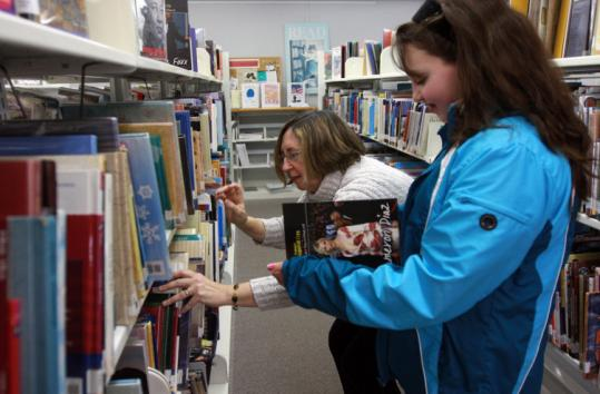 Wareham librarian Marcia Hickey aided Katelan Murphy, 11, with a selection. Last month, Wareham lost its certification.
