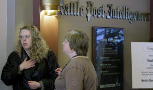 Seattle Post-Intelligencer's Marsha Milroy (left), gets word of the newspaper closing from Cecelia Goodnow yesterday.