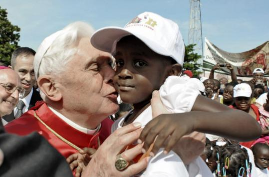 Pope Benedict XVI kissed a child during his visit in Luanda, Angola yesterday. Tens of thousands lined up to greet Benedict.